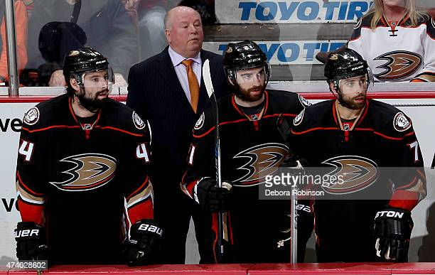 Nate Thompson head coach Bruce Boudreau Kyle Palmieri and Andrew Cogliano of the Anaheim Ducks look on from the bench during the game against the...