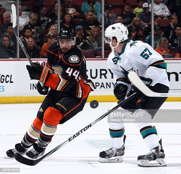 Nate Thompson of the Anaheim Ducks passes the puck up ice against Tommy Wingels of the San Jose Sharks on October 26 2014 at Honda Center in Anaheim...
