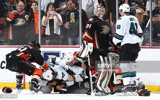 Nate Thompson of the Anaheim Ducks pulls on Adam Burish of the San Jose Sharks as he piles on with Scott Hannan on top of Andrew Cogliano in a fight...