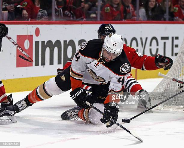 Nate Thompson of the Anaheim Ducks tries to control the puck after falling to ice in front of Viktor Svedberg of the Chicago Blackhawks at the United...