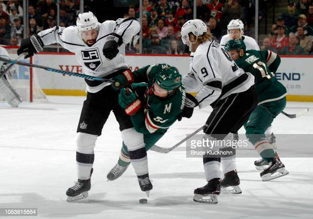 Nate Thompson of the Los Angeles Kings checks Mikael Granlund of the Minnesota Wild as Adrian Kempe of the Los Angeles Kings looks on during a game...