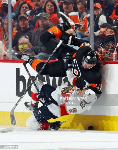 Nate Thompson of the Philadelphia Flyers checks Brandon Montour of the Florida Panthers along the boards at the Wells Fargo Center on October 23,...