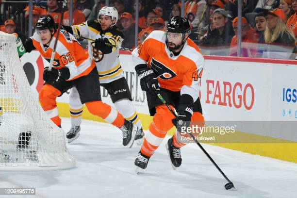 Nate Thompson of the Philadelphia Flyers skates with the puck as Nicolas AubeKubel gets checked by Matt Grzelcyk of the Boston Bruins in the third...