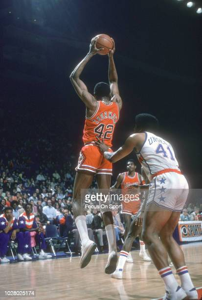Nate Thurmond of the Chicago Bulls leaps to grab a pass in front of Wes Unseld of the Washington Bullets during an NBA basketball game circa 1975 at...