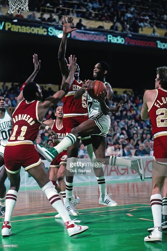 Nate 'Tiny' Archibald #7 of the Boston Celtics drives to the basket against Cliff Robinson #11 and the John Bagley #5 of the Cleveland Cavaliers during a game played in 1983 at the Boston Garden in Boston, Massachusetts.