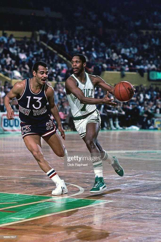 Nate 'Tiny' Archibald #7 of the Boston Celtics drives to the basket against Ed Sherod #13 of the New York Knicks during a game played in 1983 at the Boston Garden in Boston, Massachusetts.