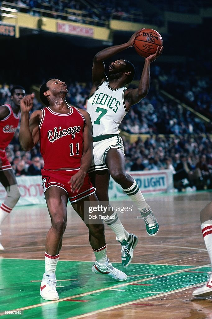 Nate 'Tiny' Archibald #7 of the Boston Celtics goes up for a shot against Tracy Jackson #11 of the Chicago Bulls during a game played in 1983 at the Boston Garden in Boston, Massachusetts.