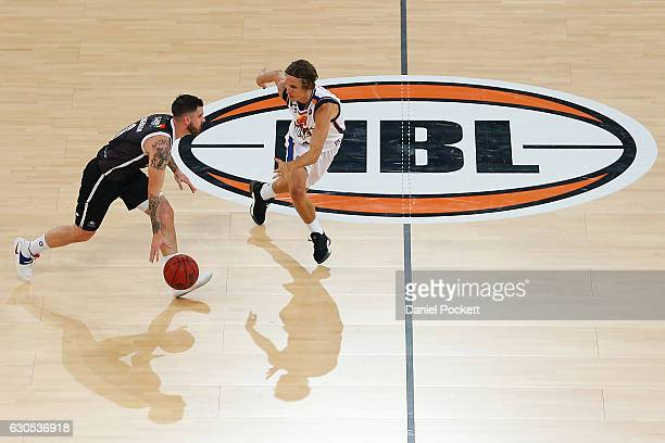 Nate Tomlinson of Melbourne United dribbles the ball past Matthew Kenyon of the Brisbane Bullets during the round 12 NBL match between Melbourne and...