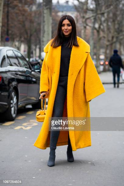 Nathalie Fanj wearing a black jumper black pants black boots yellow long coat and yellow bag is seen in the streets of Paris before the Acne Femme...