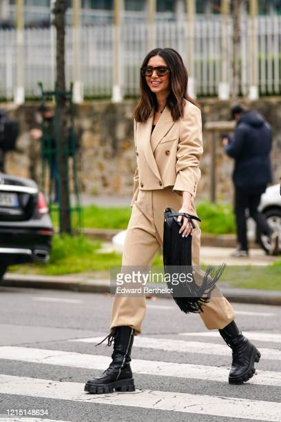 Nathalie Fanj wears sunglasses a beige double breasted jacket with four buttons pale brown pants black leather boots a black leather Loewe fringed...