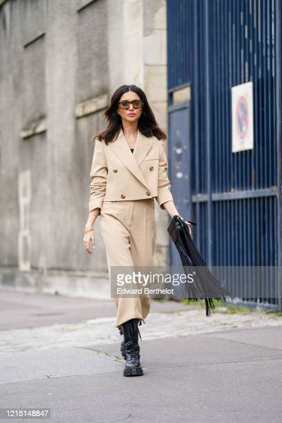 Nathalie Fanj wears sunglasses, a beige double breasted jacket with four buttons, pale brown pants, black leather boots, a black leather Loewe...