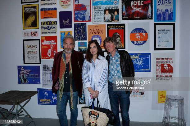 Nathalie Garcon standing between her husband JeanMarie Duprez and director Etienne Chatiliez attend Albert Koski exposes its RockRoll Posters...