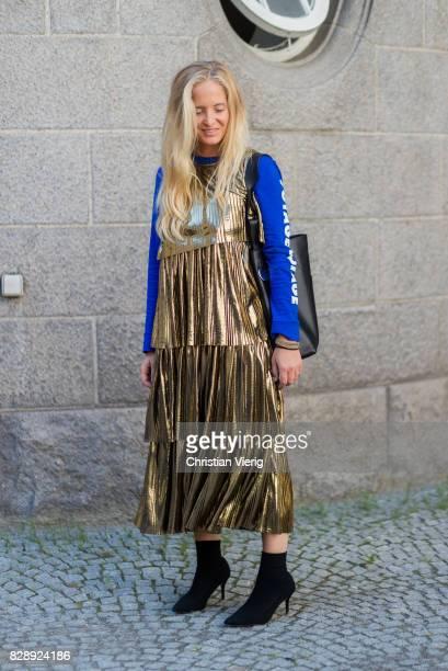 Nathalie Helgerud wearing a golden dress blue sweater black ankle boots outside Holzweiler on August 09 2017 in Copenhagen Denmark