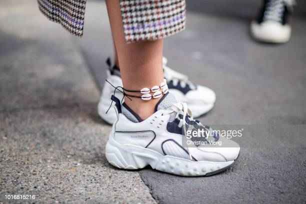Nathalie Helgerud wearing grey check coat white blouse denim skirt Acne sneakers is seen outside Epilogue during Oslo Runway SS19 on August 14 2018...