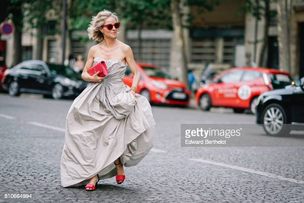 Nathalie Leroy wears red sunglasses a red bag a gray dress red heels outside the Vogue Foundation Dinner during Paris Fashion Week Haute Couture...