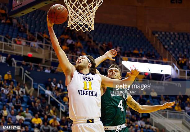 Nathan Adrian of the West Virginia Mountaineers lays one in against Zane Waterman of the Manhattan Jaspers at the WVU Coliseum on November 28 2016 in...
