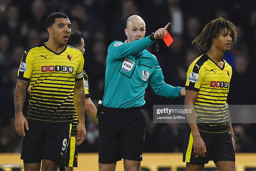 Nathan Ake (R) of Watford is shown a red card by referee Anthony Taylor (C) during the Barclays Premier League match between Watford and Tottenham Hotspur at Vicarage Road on December 28, 2015 in Watford, England.