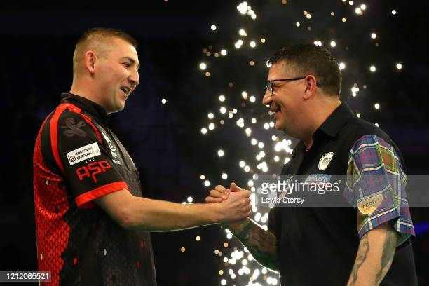 Nathan Aspinall and Gary Anderson embrace following a draw during Night Six of the Premier League Darts at the MS Bank Arena on March 12 2020 in...