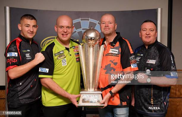 Nathan Aspinall, Michael van Gerwen, Raymond van Barneveld and Glen Durrant pose with the William Hill World Darts Championship Trophy during a Media...