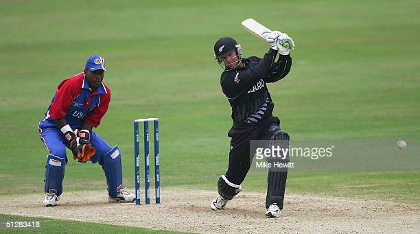 Nathan Astle of New Zealand drives for four on his way to a century as Mark Johnson of USA looks on during the ICC Champions Trophy match between New...