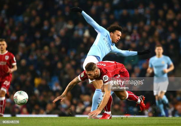 Nathan Baker of Bristol City battles with Leroy Sane of Manchester City during the Carabao Cup SemiFinal First Leg match between Manchester City and...