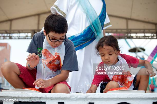 Nathan Baptista of Ayer Mass right reacted to his brother Alex slamming a lobster claw on the ground to open it during the children's lobster eating...