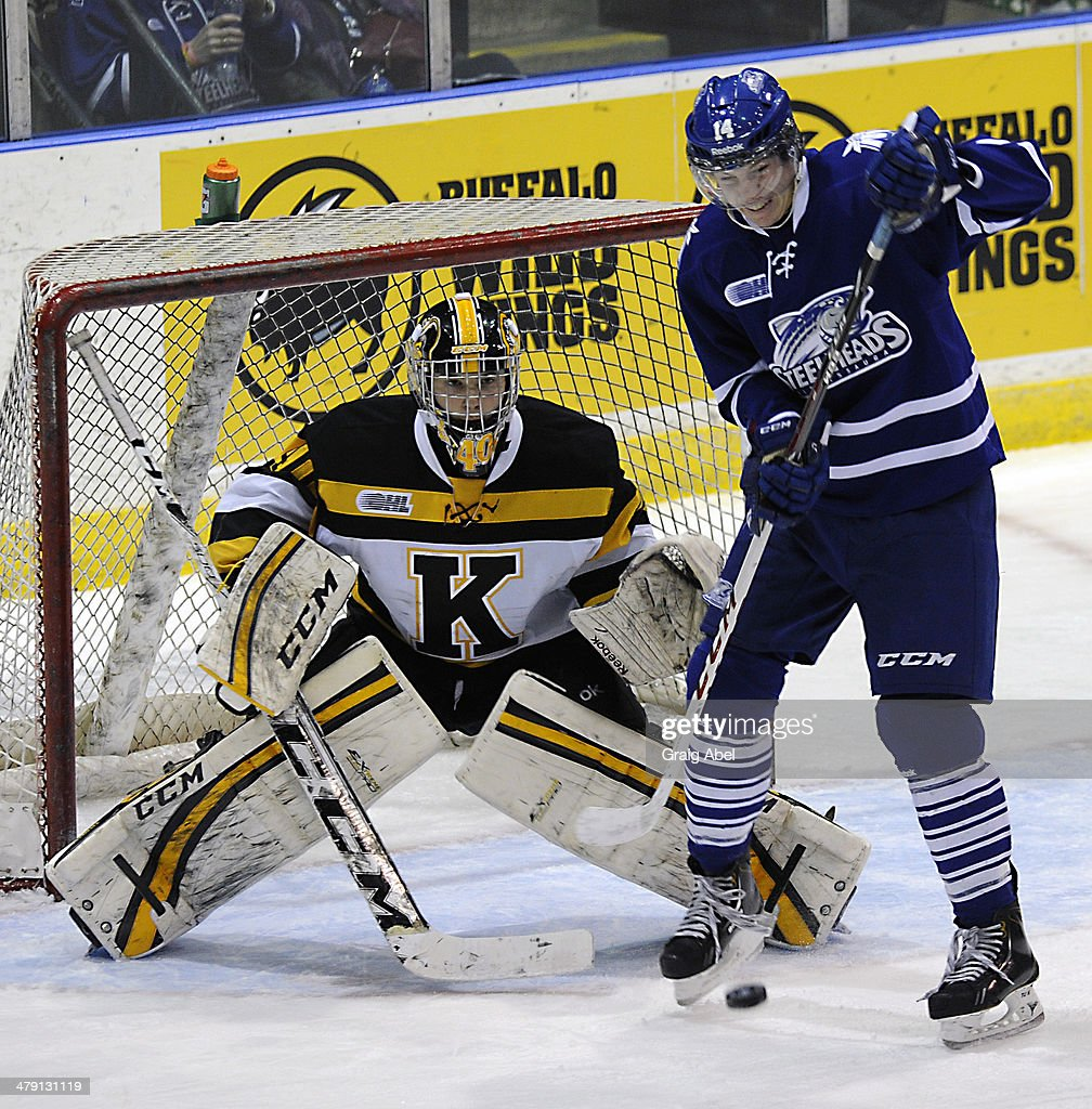 Nathan Bastian #14 of the Mississauga Steelheads look to tip the puck in front of goalie Lucas Peressini #40 of the Kingston Frontenacs during game action on March 16, 2014 at the Hershey Centre in Mississauga, Ontario, Canada.