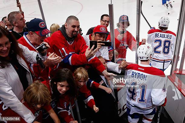 Nathan Beaulieu and Paul Byron of the Montreal Canadiens walk past fans as they take the ice for warm ups to the NHL game against the Arizona Coyotes...