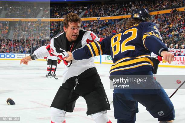 Nathan Beaulieu of the Buffalo Sabres fights Miles Wood of the New Jersey Devils during an NHL game on October 9 2017 at KeyBank Center in Buffalo...