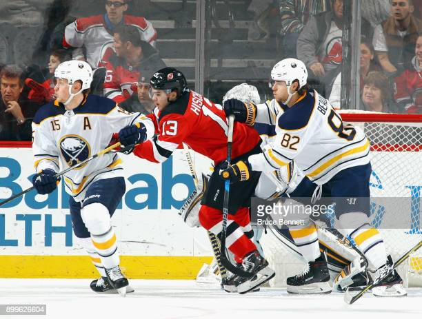 Nathan Beaulieu of the Buffalo Sabres moves Nico Hischier of the New Jersey Devils out of the crease during the first period at the Prudential Center...
