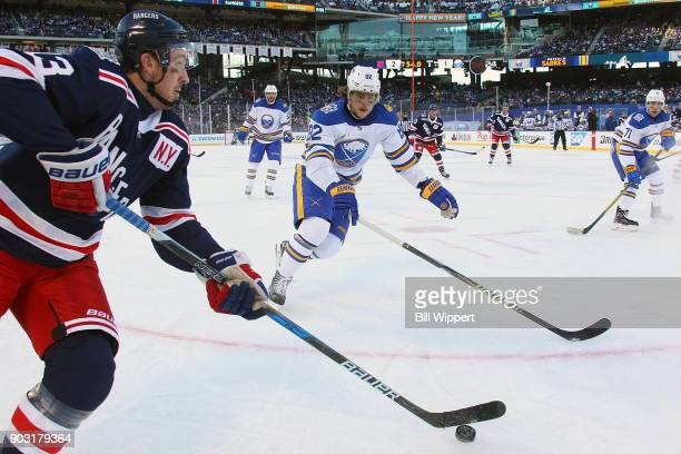 Nathan Beaulieu of the Buffalo Sabres skates against Kevin Hayes of the New York Rangers during the 2018 Bridgestone NHL Winter Classic at Citi Field...