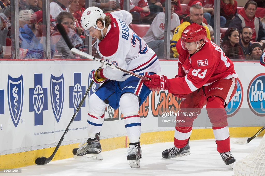 Nathan Beaulieu #28 of the Montreal Canadiens battles along the boards for the puck with Tomas Nosek #83 of the Detroit Red Wings during an NHL game at Joe Louis Arena on April 8, 2017 in Detroit, Michigan. The Canadiens defeated the Wings 3-2 in overtime.