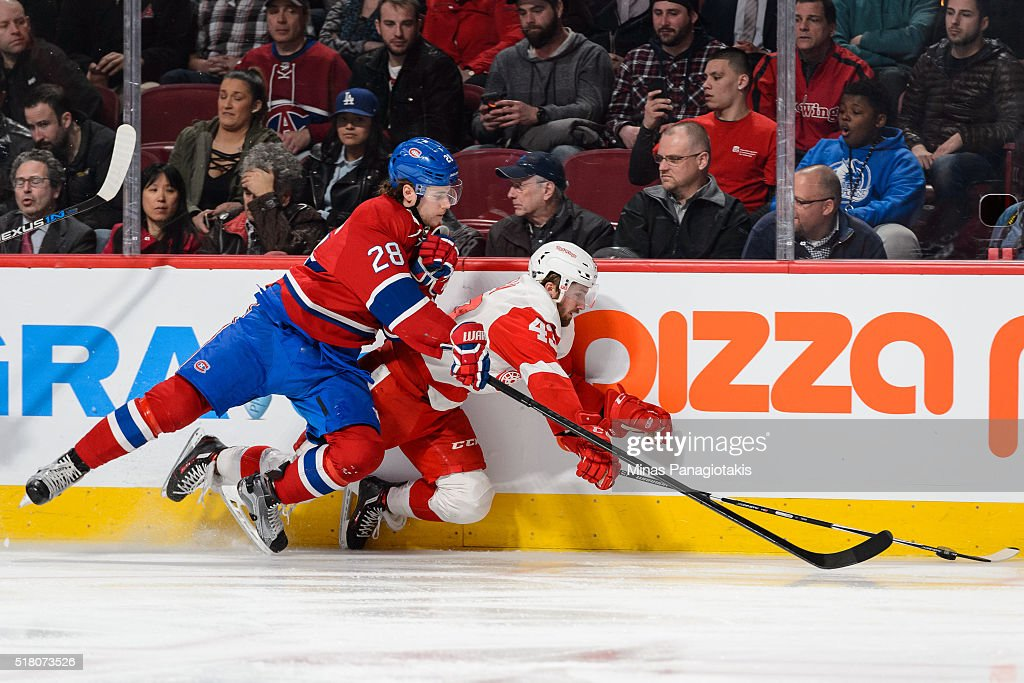 Nathan Beaulieu #28 of the Montreal Canadiens checks Darren Helm #43 of the Detroit Red Wings during the NHL game at the Bell Centre on March 29, 2016 in Montreal, Quebec, Canada. The Montreal Canadiens defeated the Detroit Red Wings 4-3.