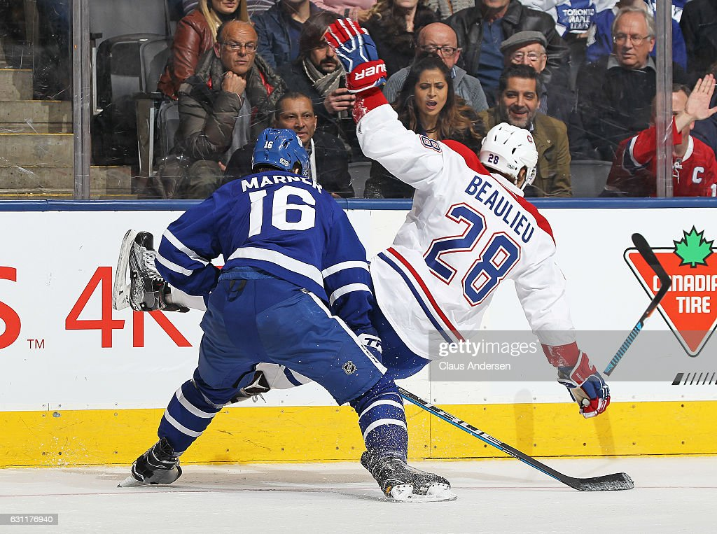 Nathan Beaulieu #28 of the Montreal Canadiens is upended by Mitchell Marner #16 of the Toronto Maple Leafs during an NHL game at the Air Canada Centre on January 7, 2017 in Toronto,Ontario, Canada. The Canadiens defeated the Maple Leafs 5-3.