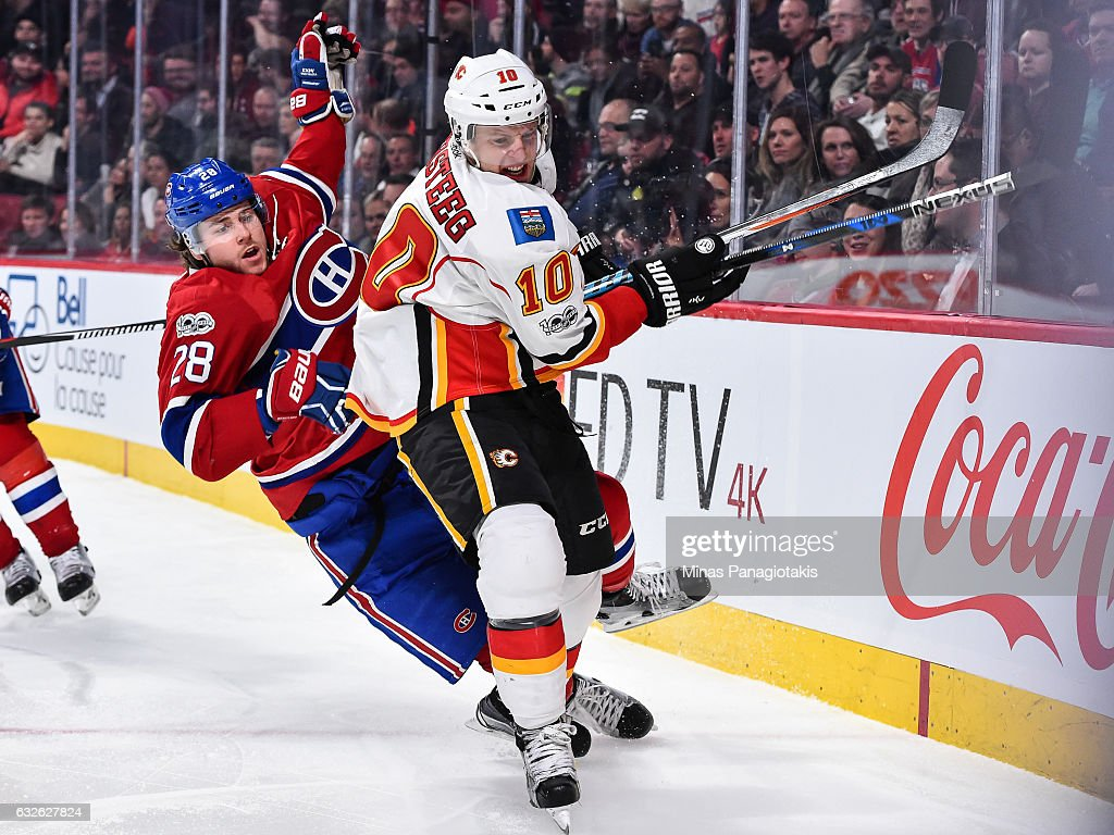 Nathan Beaulieu #28 of the Montreal Canadiens loses his balance as he skates against Kris Versteeg #10 of the Calgary Flames during the NHL game at the Bell Centre on January 24, 2017 in Montreal, Quebec, Canada. The Montreal Canadiens defeated the Calgary Flames 5-1.