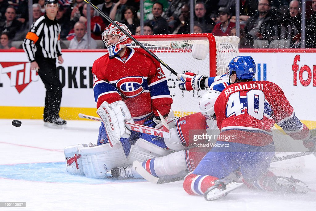 Nathan Beaulieu #40 of the Montreal Canadiens takes down Rick Nash #61 of the New York Rangers in front of goalie Carey Price #31 during the NHL game at the Bell Centre on March 30, 2013 in Montreal, Quebec, Canada. The Canadiens defeated the Rangers 3-0.