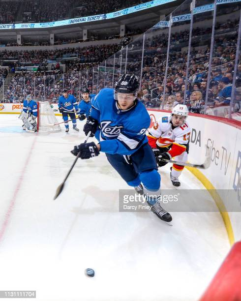 Nathan Beaulieu of the Winnipeg Jets plays the puck around the boards as Johnny Gaudreau of the Calgary Flames gives chase during third period action...