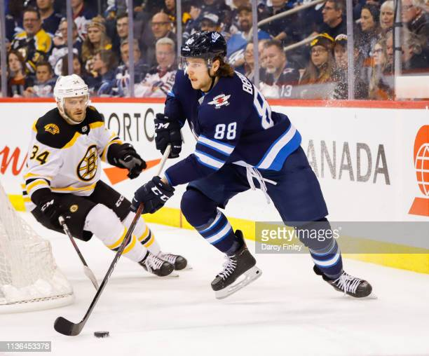 Nathan Beaulieu of the Winnipeg Jets plays the puck around the net as Paul Carey of the Boston Bruins gives chase during second period action at the...