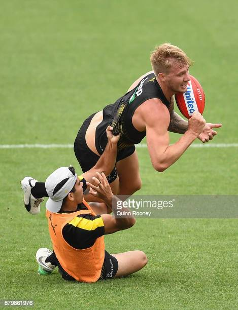 Nathan Broad of the Tigers handballs whilst being tackled during a Richmond Tigers AFL preseason training session at Swinburne Oval on November 27...