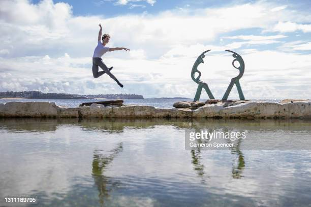 Nathan Brook poses for a portrait next to the 'Oceanides' statue by sculptor Helen Leete at Fairy Bower Rock Pool on April 07, 2021 in Sydney,...