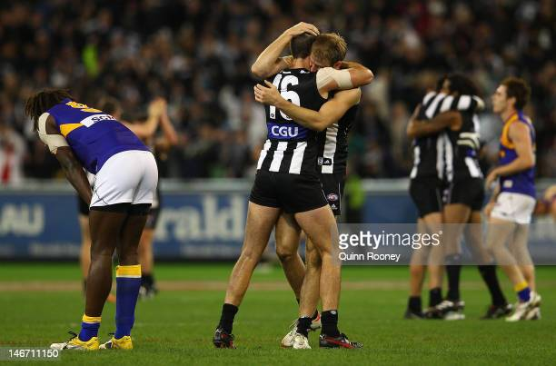 Nathan Brown and Ben Reid of the Magpies celebrates winning as Nic Naitanui of the Eagles looks dejected during the round 13 AFL match between the...