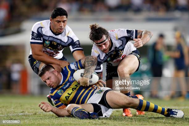 Nathan Brown of the Eels is tackled by Jason Taumalolo and Ethan Lowe of the Cowboys during the round 14 NRL match between the Parramatta Eels and...