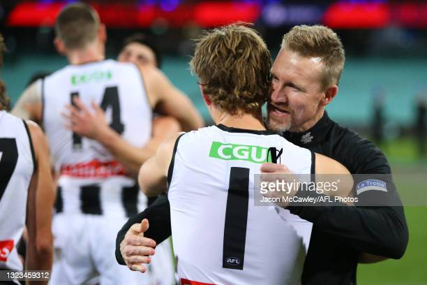 Nathan Buckley, Senior Coach of the Magpies celebrates victory with Steven May of the Demons during the round 13 AFL match between the Melbourne...
