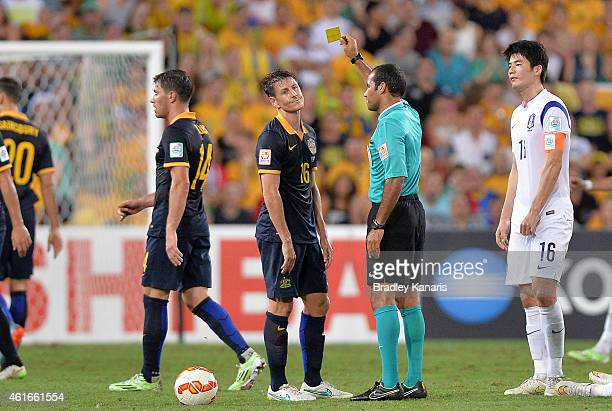 Nathan Burns of Australia is presented with a yellow card from referee Nawaf Shukralla during the 2015 Asian Cup match between Australia and Korea...