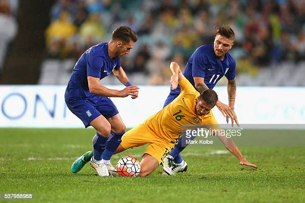 Nathan Burns of Australia is tackled by Dimitris Diamantakos and Kostas Stafylidis of Greece during the international friendly match between the...