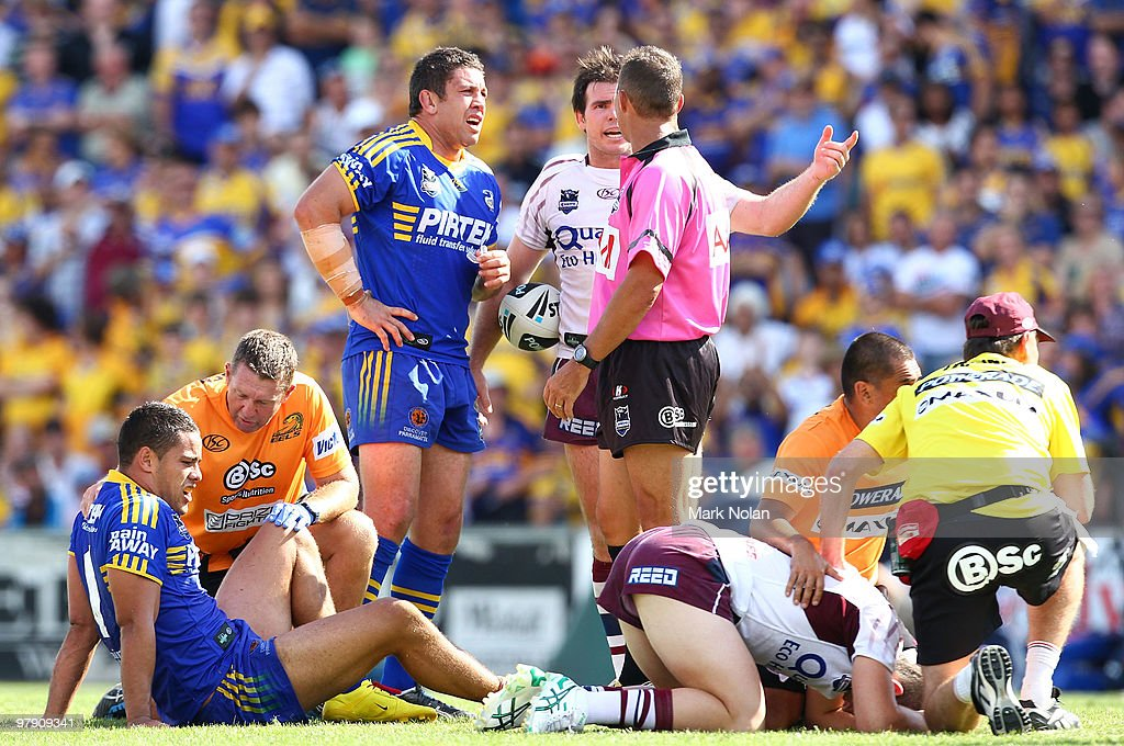 Nathan Cayless of the Eels and Jamie Lyon of the Sea Eagles speak with referee Shayne Hayne as Jarryd Hayne of the Eels and Ben Farrar of the Sea eagles receive treatment during the round two NRL match between the Parramatta Eels and the Manly Sea Eagles at Parramatta Stadium on March 21, 2010 in Sydney, Australia.