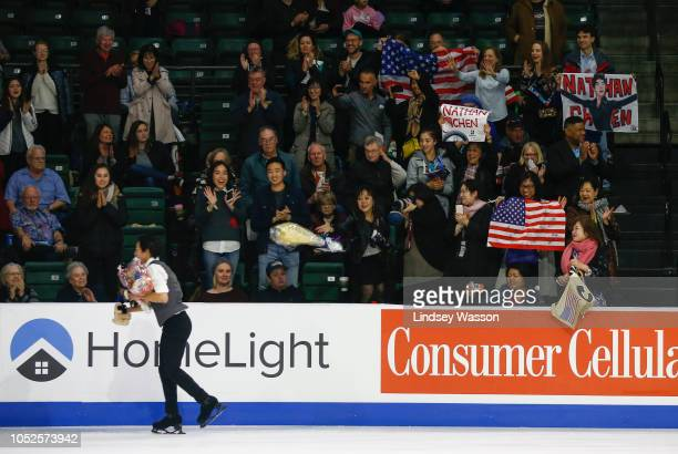 Nathan Chen of the USA collects flowers and stuffed animals from fans after performing in the Mens Short Program during day one of the ISU Grand Prix...