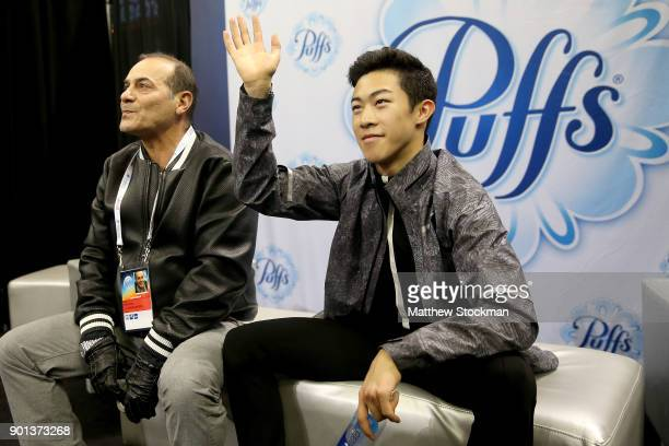Nathan Chen waits for his score in the kiss and cry with his coach Rafael Arutunian after skating in the Men's Short Program during the 2018...