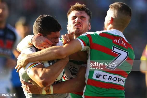 Nathan Cleary of the Panthers is tackled Angus Crichton and Adam Doueihi of the Rabbitohs during the round two NRL match between the Penrith Panthers...