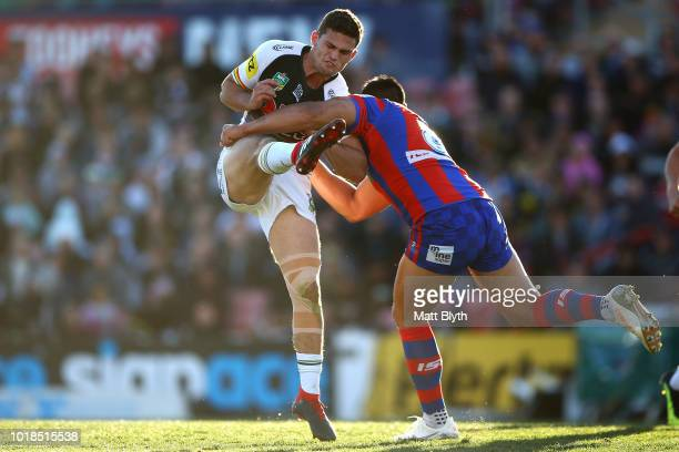 Nathan Cleary of the Panthers is tackled midair by Herman Ese'ese of the Knights during the round 23 NRL match between the Penrith Panthers and the...
